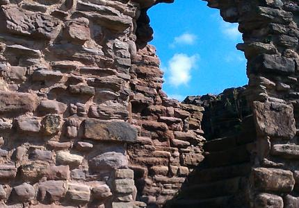 wall with hole and blue sky behind